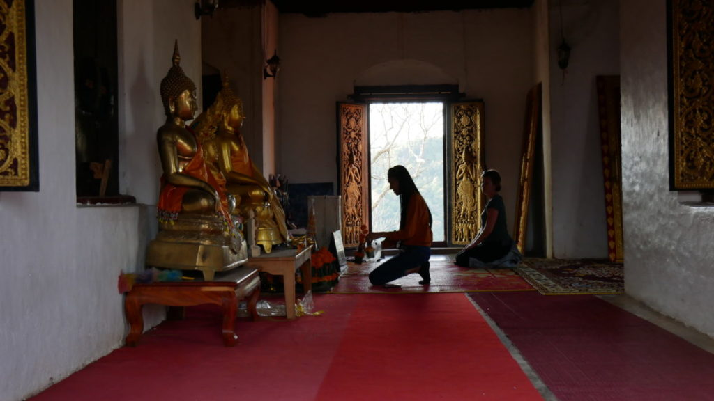 viajar a Tailandia sombra de mujer rezando en un temblo budista