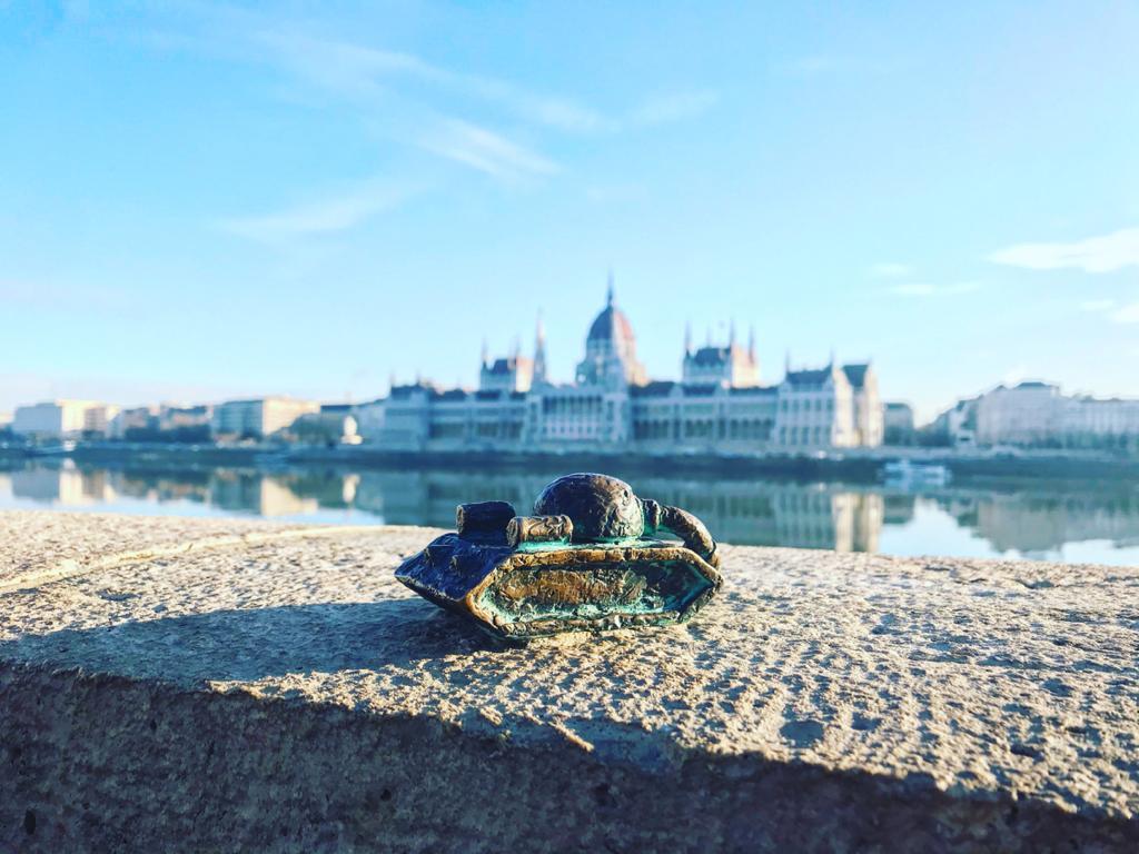 BUDAPEST, QUÉ VER EN 3 DÍAS Pequeña escultura de un tanque que nos encontramos en la orilla del Danubio mientras caminábamos por Budapest. De fondo el Parlamento.