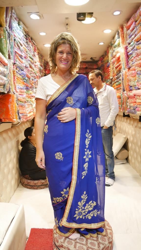 Que ver en Delhi ana_Zapatillas probándose un shari, vestido de mujer, en una tienda.