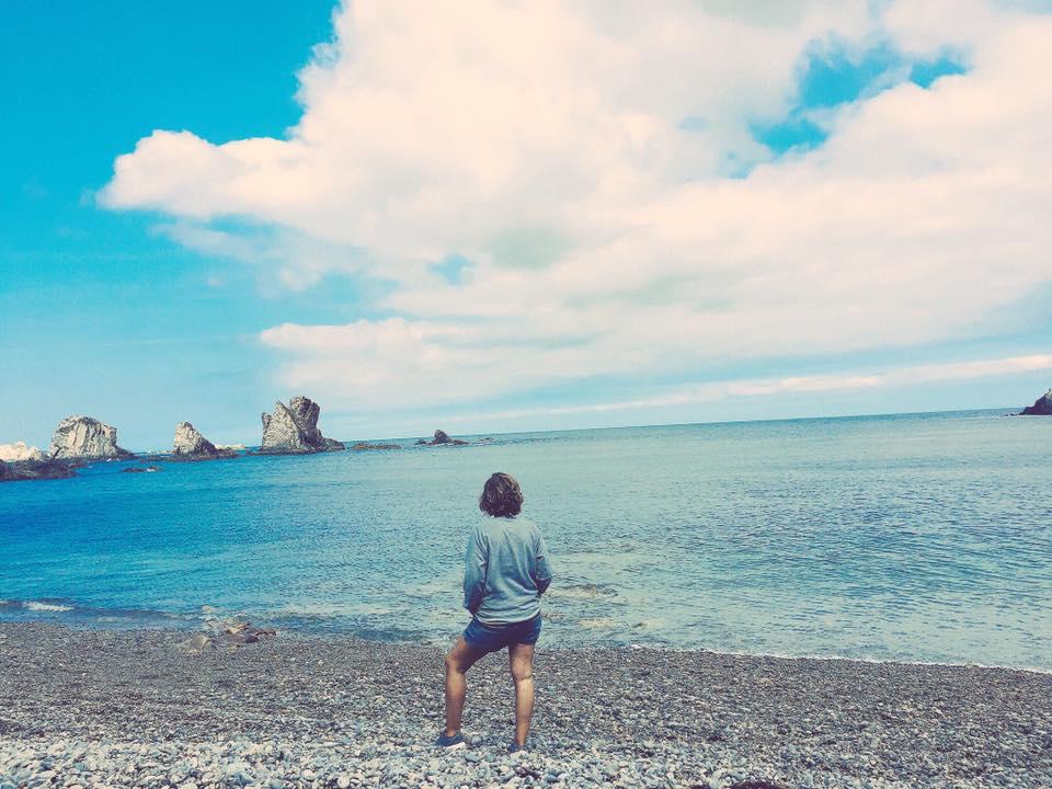 ana_zapatillas mirando al mar en la playa del silencio, cerca de cudillero